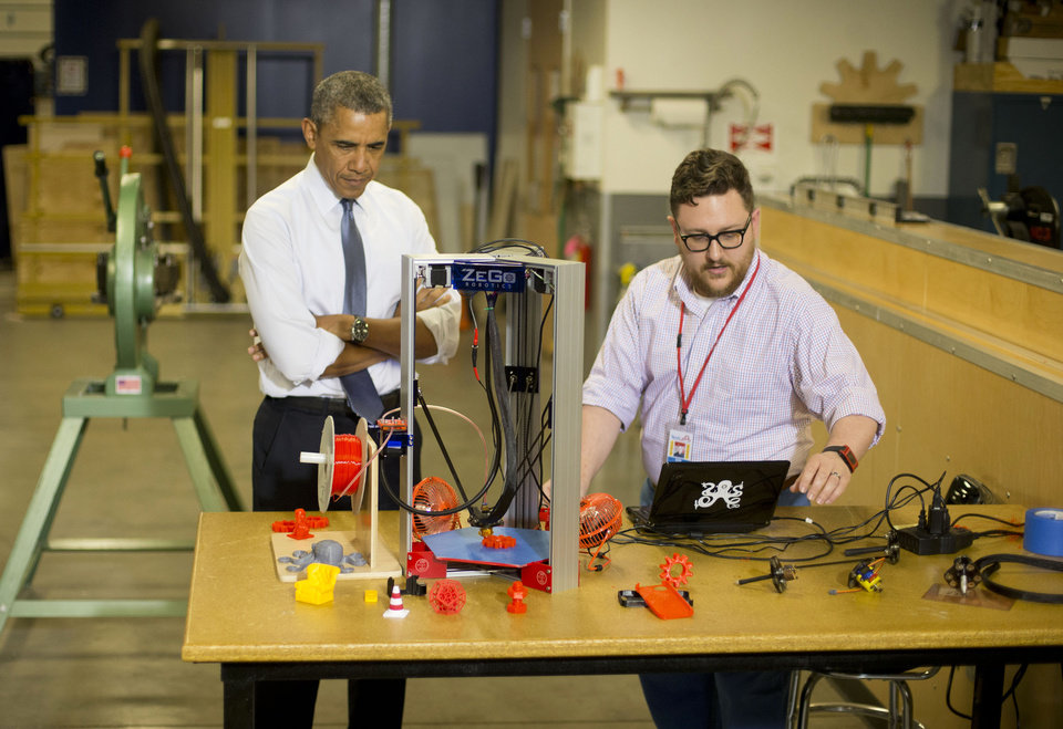 Photo - President Barack Obama is shown an example of a 3-D printer by Andy Leer during his tour of TechShop Pittsburgh, Tuesday, June 17, 2014, in Pittsburgh, Pa. Obama traveled to Pittsburgh and visited TechShop, a fabrication and prototyping studio open to the public via paid memberships, to deliver remarks on the economy. (AP Photo/Pablo Martinez Monsivais)