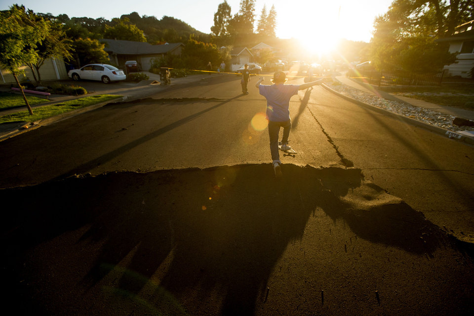 Photo - Skateboarder Bayley Lorenzen, 12, launches himself off buckled pavement in Napa, Calif., following an earthquake Sunday, Aug. 24, 2014. Officials in the city of Napa say 15 to 16 buildings are no longer inhabitable after Sunday's magnitude-6.0 earthquake, and there is only limited access to numerous other structures. (AP Photo/Noah Berger)