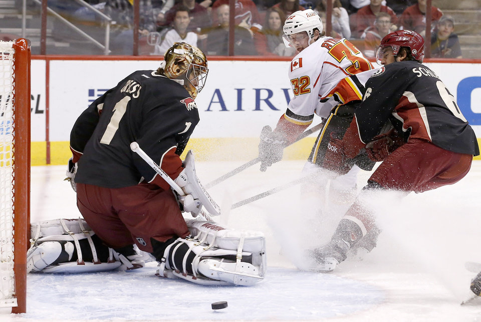 Photo - Phoenix Coyotes' Thomas Greiss (1), of Germany, makes a save on a shot by Calgary Flames' Paul Byron (32) as Coyotes' David Schlemko, right, defends during the first period of an NHL hockey game, Tuesday, Jan. 7, 2014, in Glendale, Ariz. (AP Photo/Ross D. Franklin)