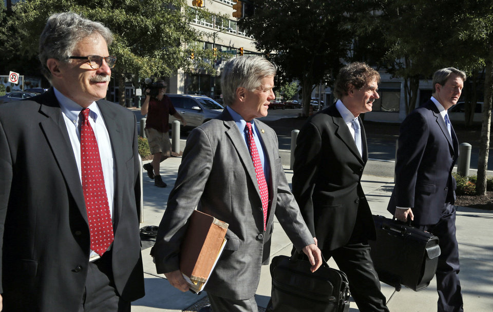 Photo - Former Virginia Gov. Bob McDonnell, second from left, arrives at federal court with his attorneys Danial Small, left, Henry Asbill second from right, and John Brownlee, right,  Wednesday, Aug. 27, 2014, in Richmond, Va.,  The defense in his corruption case is expected to rest today. McDonnell and his wife, Maureen, are charged with accepting more than $165,000 in gifts and loans from former Star Scientific Inc. CEO Jonnie Williams in exchange for promoting his company's dietary supplements.  (AP Photo/Steve Helber)