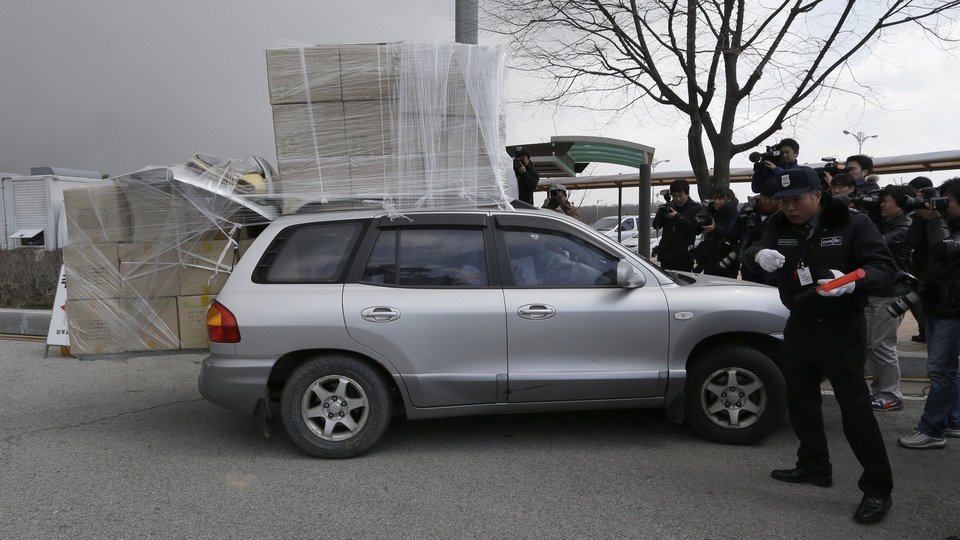 Photo - A South Korean security guard gives a direction to a vehicle from North Korea's Kaesong as a vehicle is surrounded by media at the customs, immigration and quarantine office near the border village of Panmunjom, that has separated the two Koreas since the Korean War, in Paju, north of Seoul, South Korea, Tuesday, April 9, 2013. A factory complex that is North Korea's last major economic link with the South was a virtual ghost town Tuesday after Pyongyang suspended its operations and recalled all 53,000 of its workers, cutting off jobs and a source of hard currency in its war of words and provocations against Seoul and Washington. (AP Photo/Lee Jin-man)