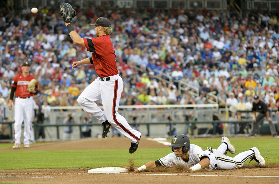 Photo - Louisville first baseman Grant Kay, left, leaps to catch the ball as Vanderbilt's Vince Conde, right, slides back to first base on a pickoff-attempt in the third inning of an NCAA baseball College World Series game in Omaha, Neb., Saturday, June 14, 2014. (AP Photo/Ted Kirk)