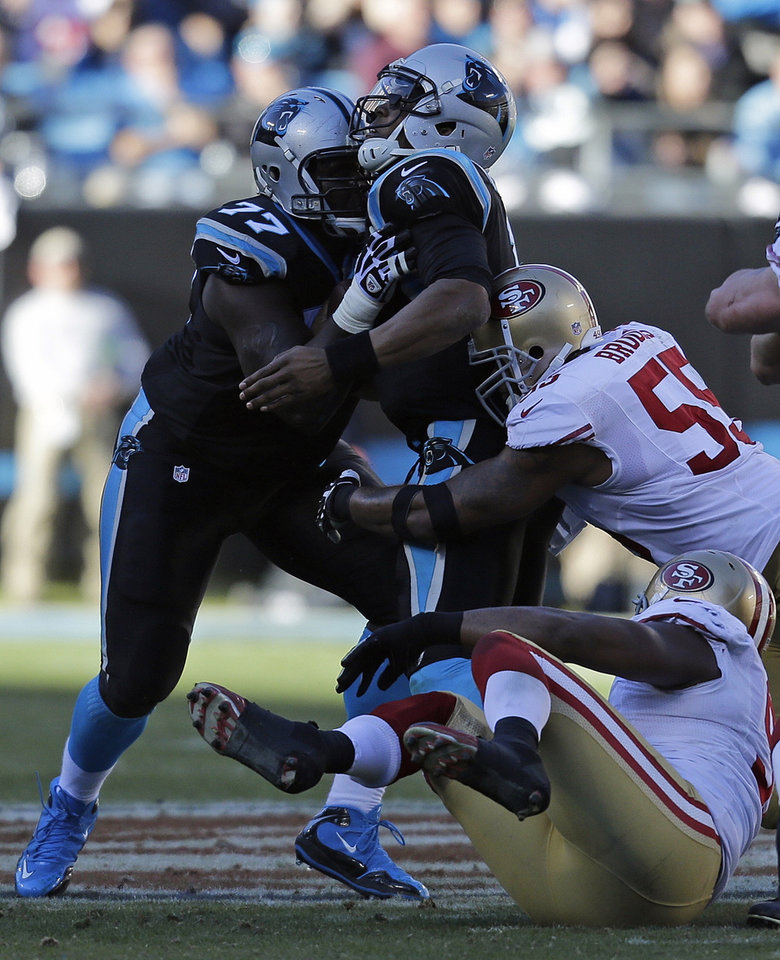 Photo - Carolina Panthers quarterback Cam Newton (1) runs into Carolina Panthers tackle Byron Bell (77) as San Francisco 49ers outside linebacker Ahmad Brooks (55) makes the sack during the second half of a divisional playoff NFL football game, Sunday, Jan. 12, 2014, in Charlotte, N.C. (AP Photo/Chuck Burton)