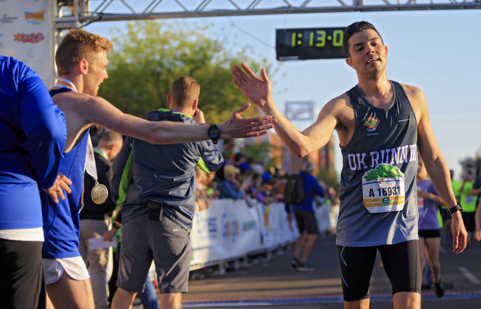 Photo - Jazz Carreon is met with a high-five as he crosses the finish line after completing the half marathon during the Oklahoma City Marathon in Oklahoma City, Okla. on Sunday, April 29, 2018.  . Photo by Chris Landsberger, The Oklahoman