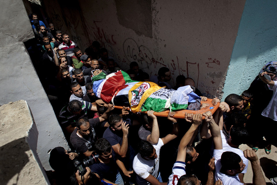 Photo - Mourners carry the body of slain Palestinian Ahmad Arafat Sabarin, 20, who was killed by Israeli army fire early Monday during a confrontation between stone throwers and soldiers, at his funeral procession in the Palestinian refugee camp of Jalazoun, on the outskirts of the West Bank city of Ramallah, Monday, June 16, 2014. Israeli troops on Monday rounded up dozens more senior Hamas activists and killed a Palestinian in a clash with stone throwers — part of a feverish search for three kidnapped Israeli teenagers who Israel alleges were seized by the Islamic militant group. (AP Photo/Nasser Nasser)