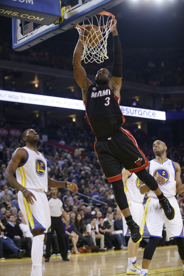 Miami Heat's Dwyane Wade (3) dunks next to Golden State Warriors' Festus Ezeli (31) and Jarrett Jack (2) during the first half of an NBA basketball game in Oakland, Calif., Wednesday, Jan. 16, 2013. (AP Photo/Marcio Jose Sanchez)