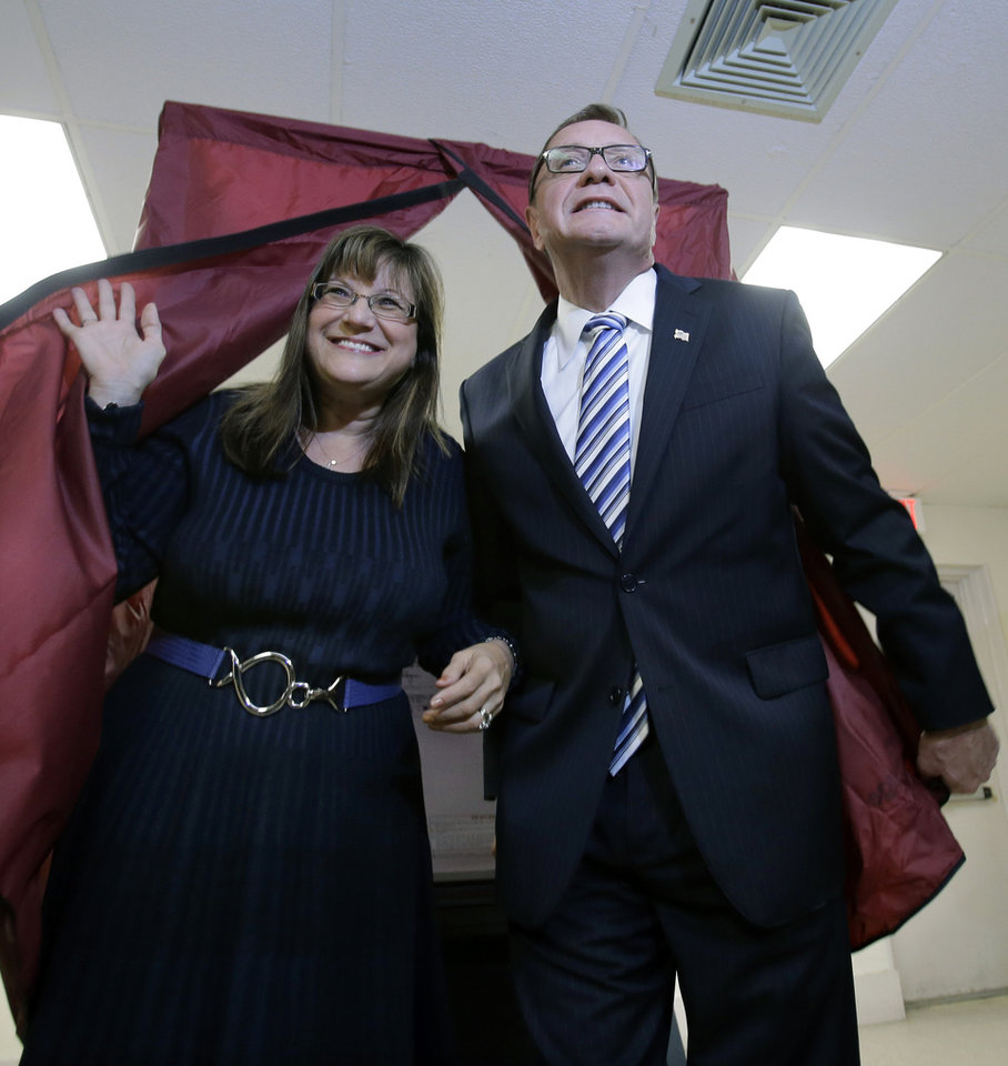 Photo - Lorraine Rossi Lonegan exits a voting booth with her husband, Republican senate candidate Steve Lonegan, in Bogota, N.J., Wednesday, Oct. 16, 2013. In a race for U.S. Senate that touched upon a candidate's tweets with a stripper and a political strategist's profanity-laced rant, perhaps it's only fitting that the outcome will be decided on a Wednesday in October. The two-month campaign in New Jersey between Democrat Cory Booker and Lonegan ends amid a lingering federal government shutdown, underscoring the different approaches each would take as a senator. (AP Photo/Mel Evans)