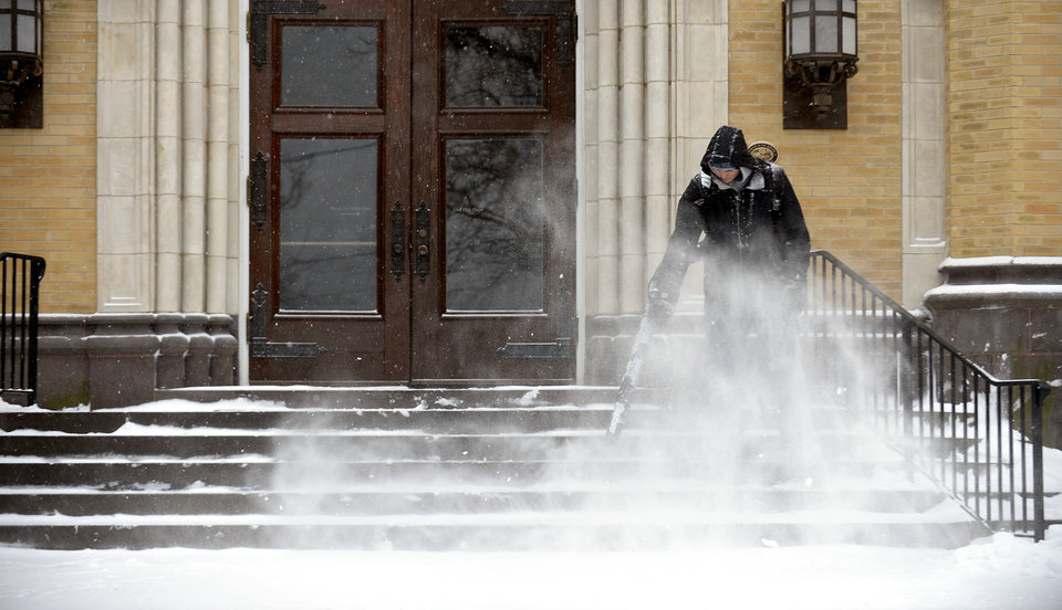 Photo - Dan Schramm, a senior at Lebanon Valley College, uses a backpack blower to clear snow off the steps of the humanities building on Tuesday, Jan. 21, 2014, in Annville Township, Pa. The National Weather Service predicts the storm could drop 8 to 12 inches of snow followed by bitterly cold temperatures. (AP Photo/Lebanon Daily News, Jeremy Long)  THE PATRIOT-NEWS OUT