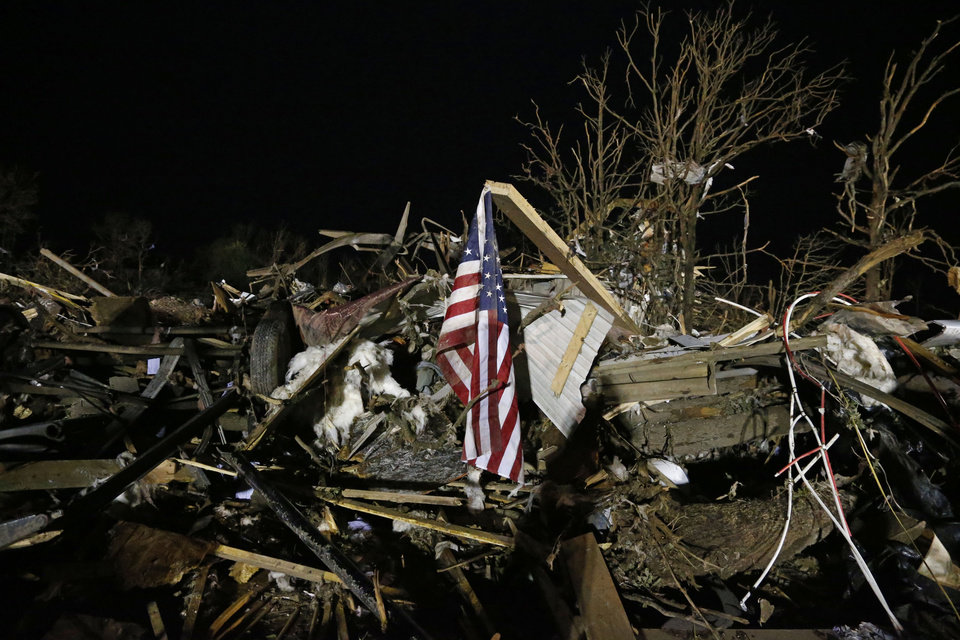 Photo - A flag flies in the debris of a mobile home after a tornado struck a mobile home park near Dale, Okla., Sunday, May 19, 2013. (AP Photo Sue Ogrocki)