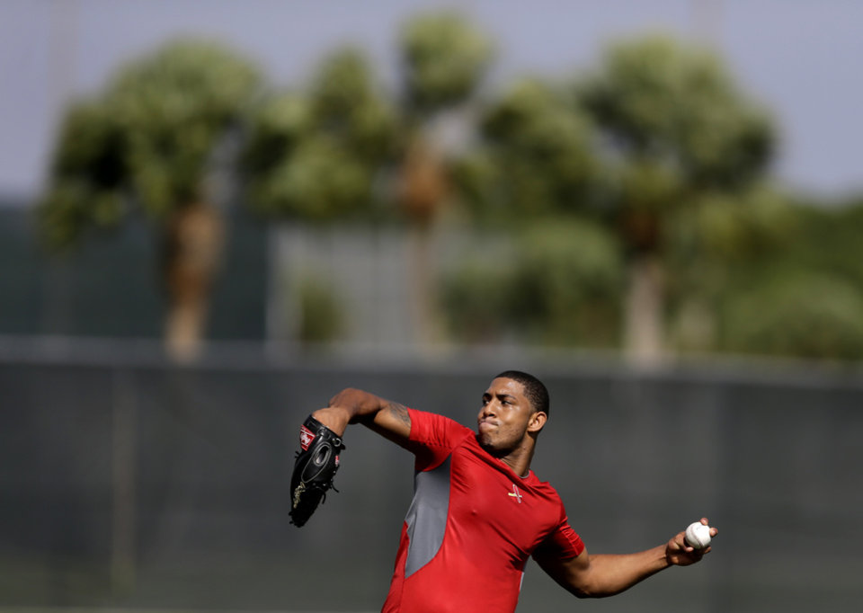 Photo - St. Louis Cardinals outfielder Oscar Taveras throws during an informal spring training baseball practice Wednesday, Feb. 12, 2014, in Jupiter, Fla. Cardinals pitchers and catchers first official practice is scheduled for Thursday. (AP Photo/Jeff Roberson)