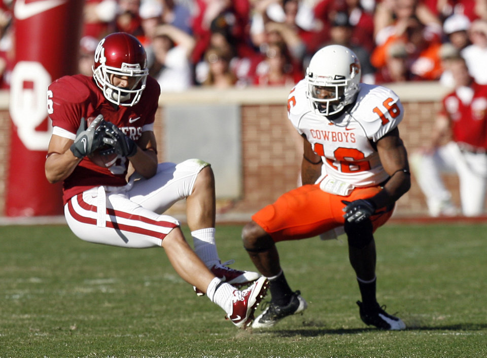 Photo - OU's Cameron Kenney (6) catches a pass in front of OSU's Perrish Cox (16) during the second half of the Bedlam college football game between the University of Oklahoma Sooners (OU) and the Oklahoma State University Cowboys (OSU) at the Gaylord Family-Oklahoma Memorial Stadium on Saturday, Nov. 28, 2009, in Norman, Okla. Photo by Sarah Phipps, The Oklahoman