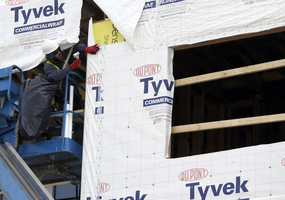 Photo - In this March 26, 2014 photo, a builder works on a home under construction in northwest Chicago. The Conference Board reports on its index of leading economic indicators for March on Monday, April 21, 2014. (AP Photo/Nam Y. Huh)