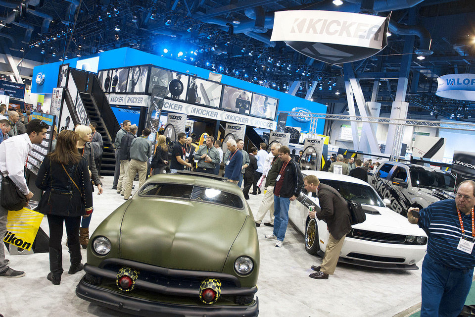 Attendees of the 2013 International CES consumer electronics show on Wednesday look at products offered by Stillwater-based Kicker at the company�s mobile audio booth in Las Vegas. Photo by PAUL RIEDL, The Oklahoman
