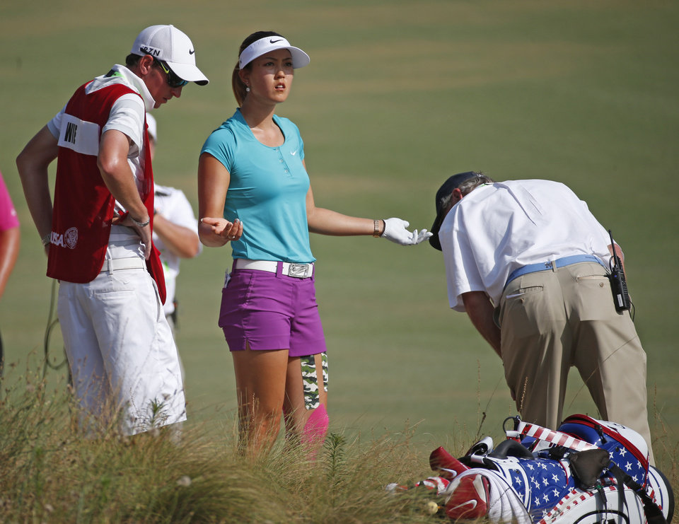Photo - Michelle Wie, center, reacts as she looks for her ball on the 16th hole during the final round of the U.S. Women's Open golf tournament in Pinehurst, N.C., Sunday, June 22, 2014. (AP Photo/John Bazemore)