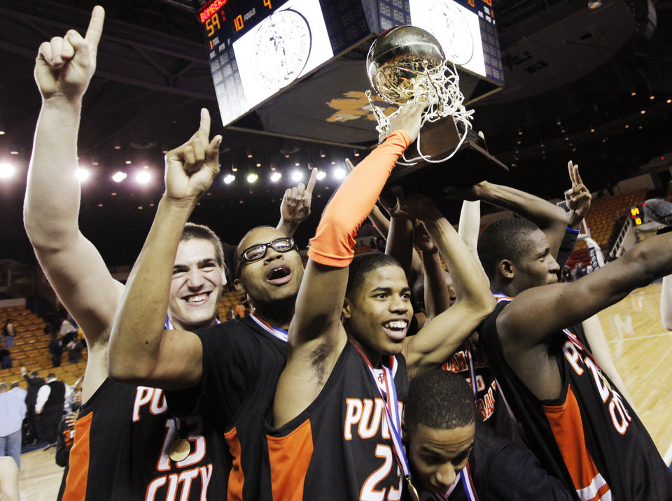 The Putnam City Pirates celebrate with the gold ball championship trophy after the Class 6A high school basketball state tournament final between Putnam City and Midwest City at the ORU Mabee Center in Tulsa, Okla., Saturday, March 13, 2010. Putnam City won, 68-59. Photo by Nate Billings, The Oklahoman