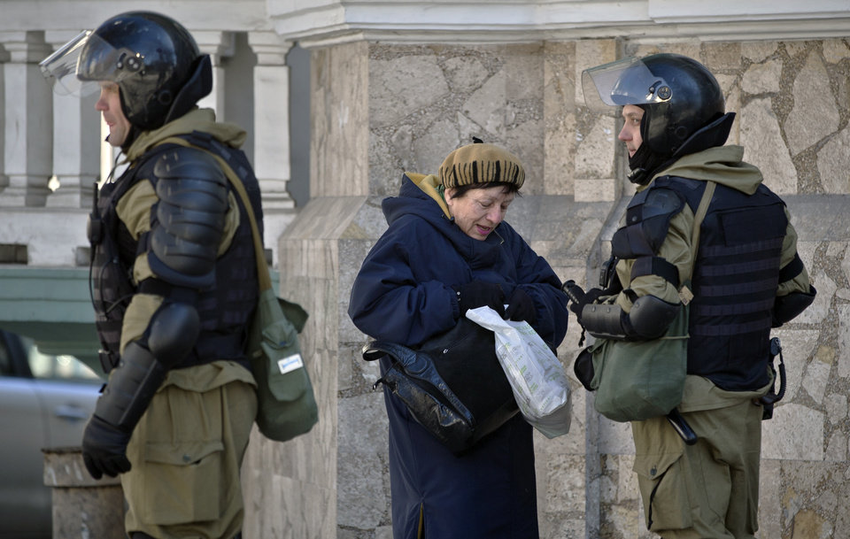 Photo - A woman searches for her identity documents standing next to armed men in riot gear, that were performing identity and hand bag checks on people walking near the building of Crimea's regional parliament in Simferopol, Ukraine, Monday, March 17, 2014. Crimea's parliament on Monday declared the region an independent state, after its residents voted overwhelmingly to break off from Ukraine and seek to join Russia. (AP Photo/Vadim Ghirda)