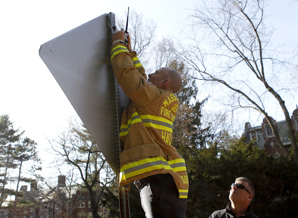 Photo - A member of the Massachusetts Department of Fire Services Haz-Mat crew affixes a device to the back of a street sign in front of Wellesley College before the start of the 118th Boston Marathon Monday, April 21, 2014 in Wellesley, Mass.. (AP Photo/Mary Schwalm)