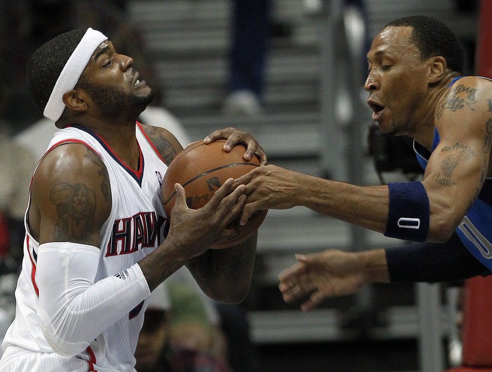 Atlanta Hawks forward Josh Smith, left, and Dallas Mavericks forward Shawn Marion, right, struggle for control of the ball during the second half of an NBA basketball game on Thursday, April 26, 2012, in Atlanta. (AP Photo/John Bazemore)