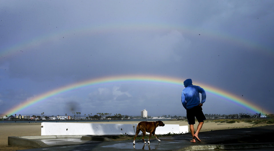 Photo - Scott Kimball walks with his dog Payton in front of a double rainbow, Tuesday, Nov. 3, 2015, in San Diego. Light rain fell on parts of San Diego county Tuesday, amid scattered rays of sunshine, providing the county with occasional rainbows. (AP Photo/Gregory Bull)