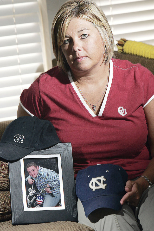Photo - Angie Stewart-Mazza holds hats  and a photo of her son Michael, who died of a drug overdose.  PHOTO BY JACONNA AGUIRRE, THE OKLAHOMAN
