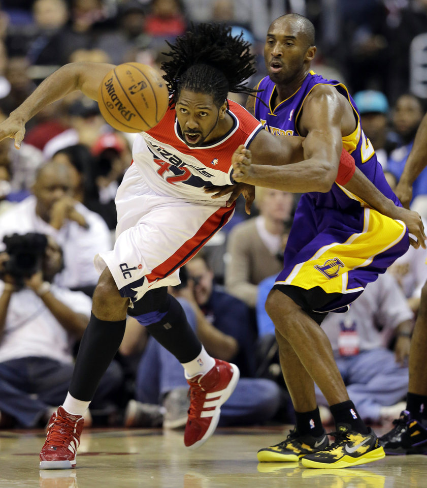 Photo - Washington Wizards center Nene, from Brazil, and Los Angeles Lakers guard Kobe Bryant go for the loose ball in the first half of an NBA basketball game Friday, Dec. 14, 2012 in Washington. (AP Photo/Alex Brandon)