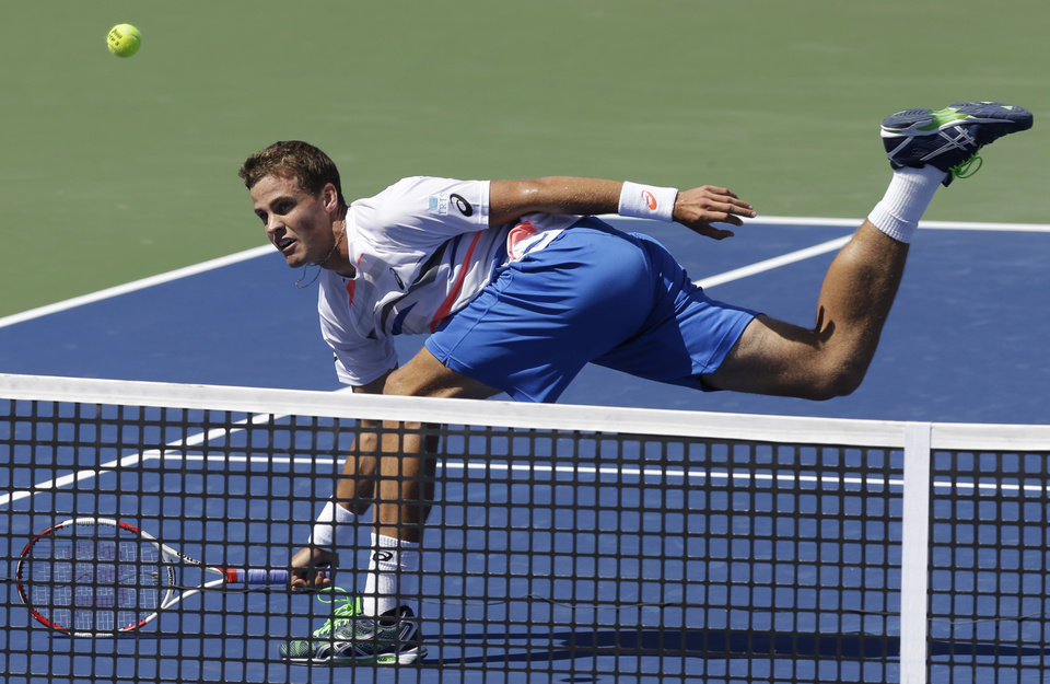 Photo - Vasek Pospisil, from Canada, volleys against Roger Federer, from Switzerland, during a match at the Western & Southern Open tennis tournament, Wednesday, Aug. 13, 2014, in Mason, Ohio. (AP Photo/Al Behrman)