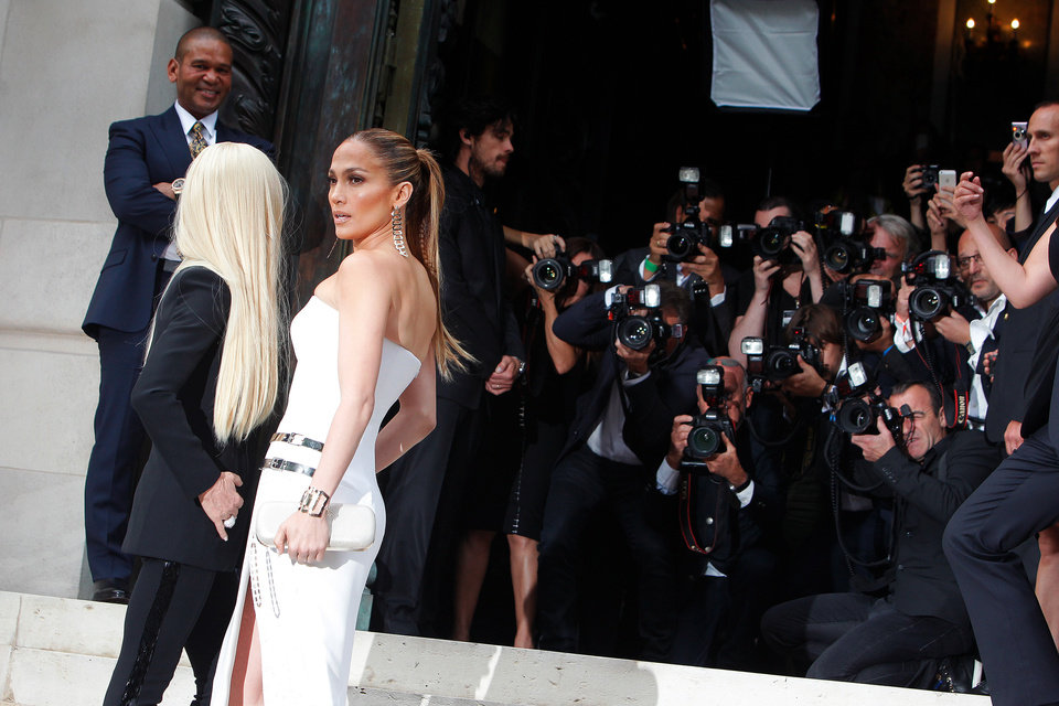 Photo - Singer Jennifer Lopez, center, and Italian fashion designer Donatella Versace, pose for photographers prior to the Atelier Versace Fall Winter 2014-15  Haute Couture fashion collection, presented in Paris, Sunday, July 6, 2014. (AP Photo/Thibault Camus)