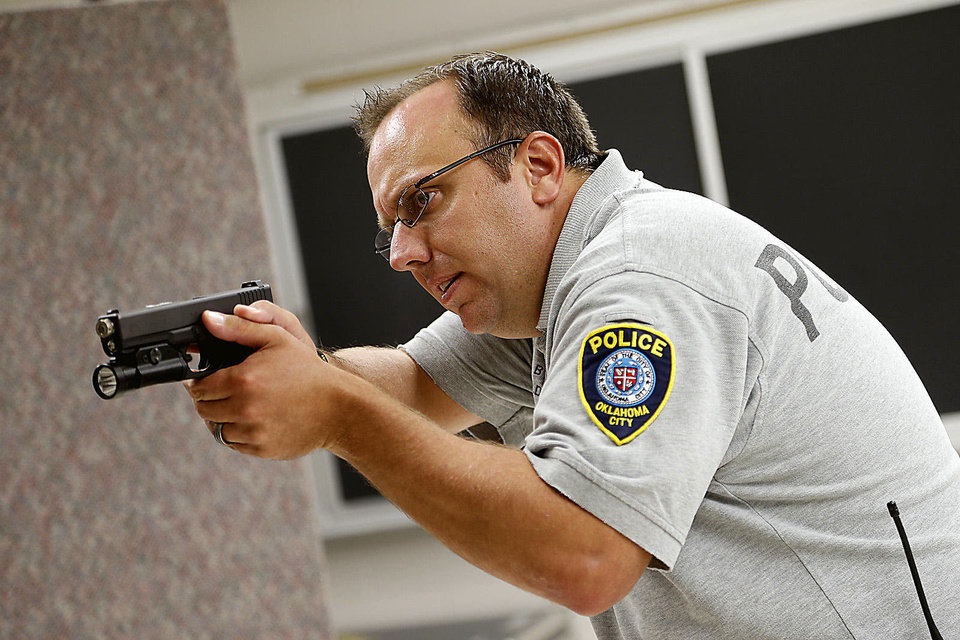Oklahoma CIty police Sgt. Shawn Byrne goes through a shooting simulator scenario.  Photo by BRYAN TERRY, THE OKLAHOMAN