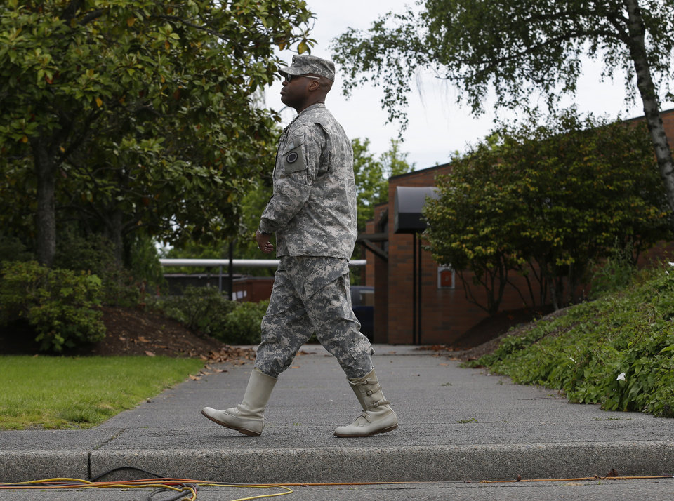 Photo - Lt. Col. Gary Dangerfield, a public affairs officer at Joint Base Lewis McChord, Wash., walks Wednesday, June 5, 2013, outside the building housing the military courtroom where U.S. Army Staff Sgt. Robert Bales was taking part in a plea hearing. Bales is accused of 16 counts of premeditated murder and six counts of attempted murder for a pre-dawn attack on two villages in Kandahar Province in Afghanistan in March, 2012. (AP Photo/Ted S. Warren)