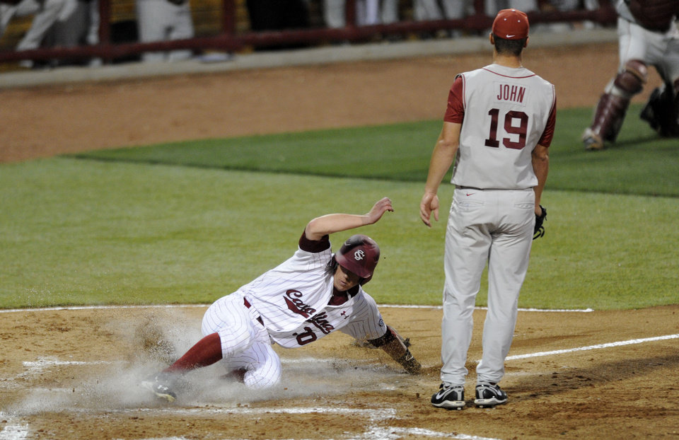 Photo - South Carolina's Erik Payne, left, slides safely into home plate as Oklahoma's pitcher Jordon Johns (19) waits on the throw in the third inning of an NCAA college super regional baseball tournament game in Columbia, S.C., Saturday, June 9, 2012. (AP Photo/Mary Ann Chastain) ORG XMIT: SCMC102