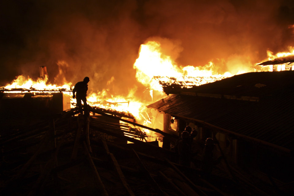 Photo - A firefighter works on a roof of a wooden building while a fire ravages ancient Dukezong town in Shangri-la county, in southwestern China's Yunnan province, Saturday Jan. 11, 2014. The 10-hour inferno has razed the ancient Tibetan town in the province that's popular with tourists. (AP Photo) CHINA OUT