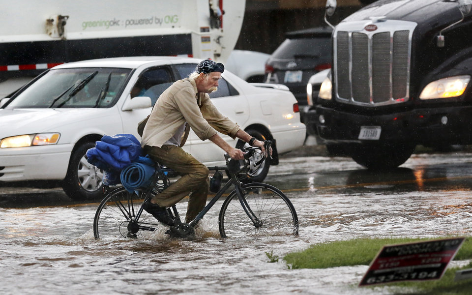 Photo - A man navigates his bicycle through high water as he crosses SW 29 Street after heavy rains overwhelmed stormwater drainage systems and flooded streets, requiring  high water rescues in Oklahoma City as another round of severe storms passes through the metro.