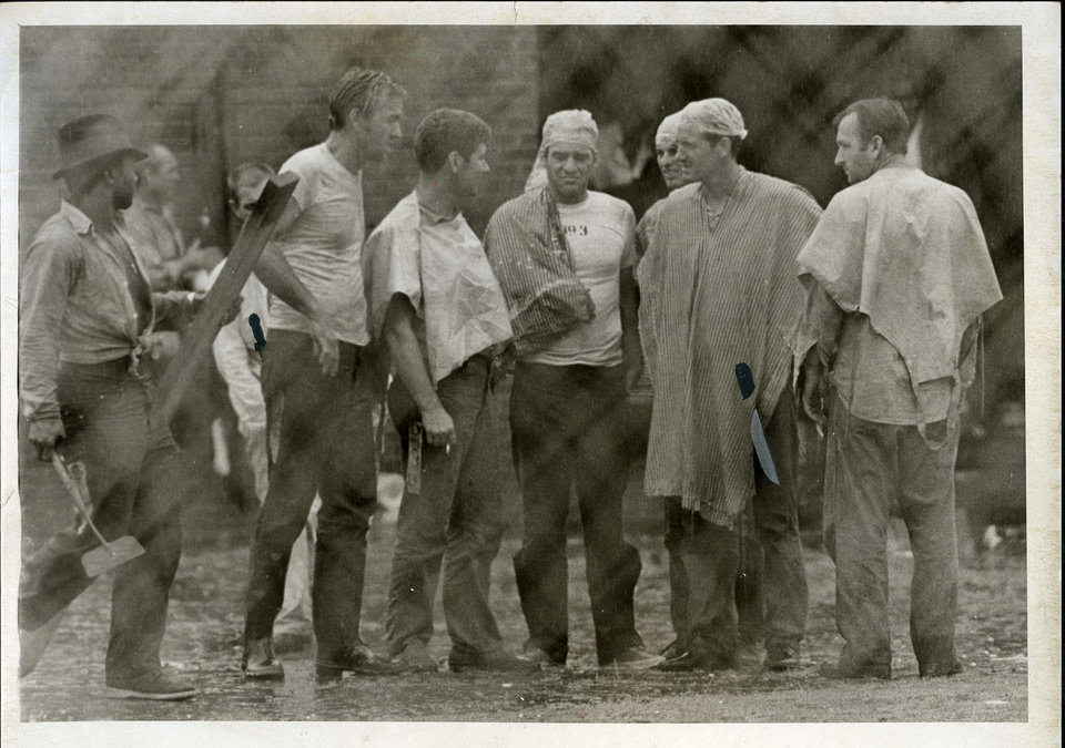 Photo - PENAL INSTITUTION / OKLAHOMA STATE PENITENTIARY / McALESTER PRISON RIOT 1973: Inmates wait Monday for a cell block shakedown to be completed. Two in this group (the second from the left and the second from the right) carry knives partially hidden by their clothing. Some inmates say they did not participate in the riot and carry weapons because they fear reprisals from those who did. These men are outside the main prison walls, but behind a tall, chainlink fence. Staff Photo by Jim Argo Original photo taken 07/30/1973, published 07/31/1973 in The Daily Oklahoman    ORG XMIT: OKC1307251029073401