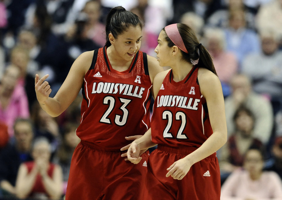 Photo - Louisville's Shoni Schimmel, left, and sister Jude Schimmel talk to one another after a missed pass between the two during the first half of an NCAA women's college basketball game against Connecticut, Sunday, Feb. 9, 2014, in Storrs, Conn. Connecticut won 81-64. (AP Photo/Jessica Hill)