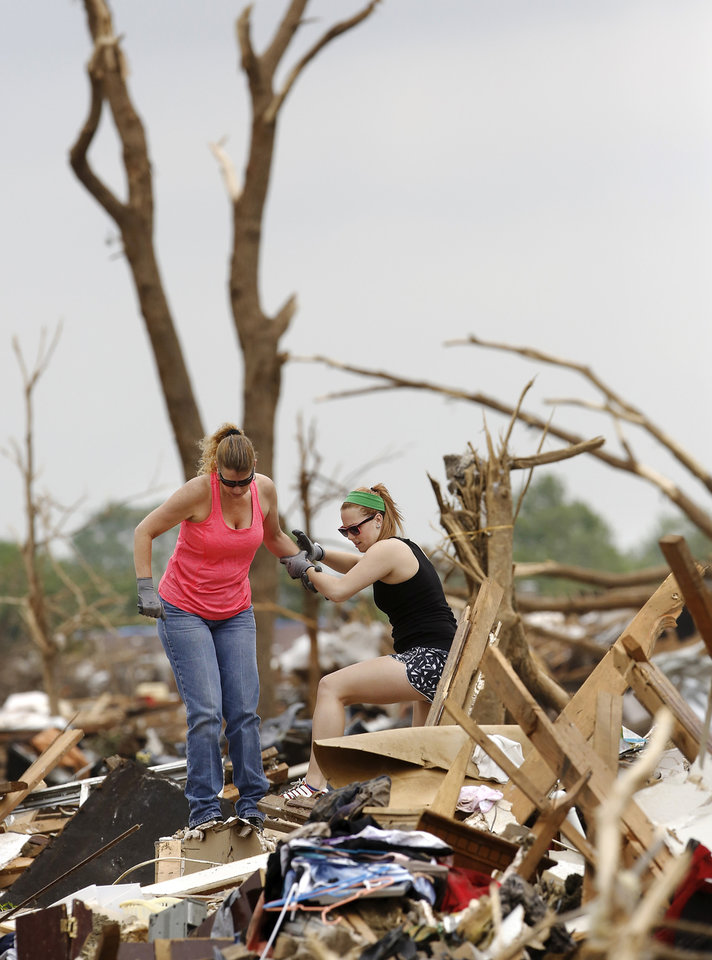 Photo - Lori Forston, left, helps her daughter, Ashton Forston, as she climbs over the rubble of Trina Minnick's house. The Forstons were among several volunteers who showed up to help Minnick search for valuable items after her home was demolished by a tornado earlier this week. Minnick has an injured foot and sat in a chair watching and talking to the volunteers as they worked. Volunteers from various parts of the country joined Oklahomans in assisting residents on Saturday,  May 25, 2013, doing whatever was needed to remove debris and salvage items from this neighborhood east of Santa Fe, north of SW 19 Street.  An EF5 tornado leveled many neighborhoods in Moore and southwest Oklahoma City last Monday.   Photo  by Jim Beckel, The Oklahoman.