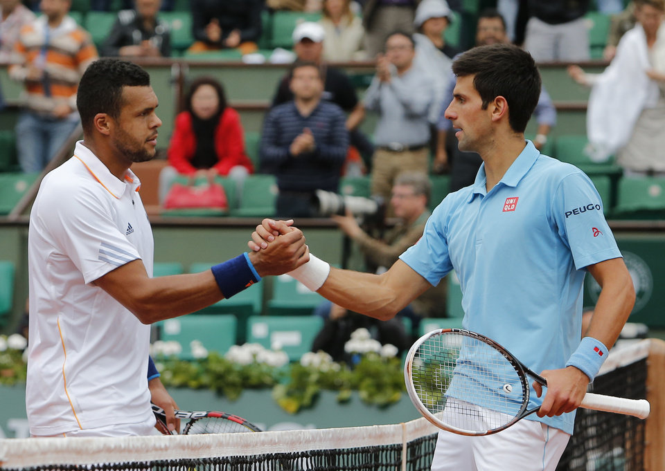 Photo - Serbia's Novak Djokovic, right, shakes hands with France's Jo-Wilfried Tsonga after their fourth round match of  the French Open tennis tournament at the Roland Garros stadium, in Paris, France, Sunday, June 1, 2014. Djokovic won 6-1, 6-4, 6-1. (AP Photo/David Vincent)
