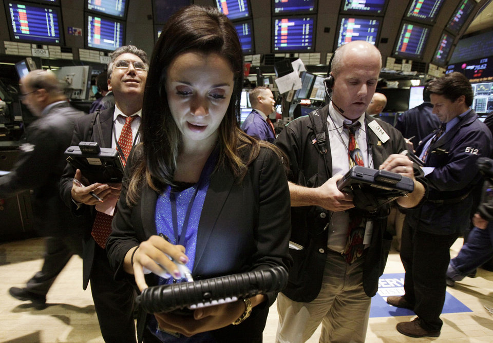Lucia Cuttone works with fellow traders on the floor of the New York Stock Exchange Tuesday, Oct. 9, 2012. Another dire prediction about global economic growth is sending stocks lower on Wall Street in early trading. (AP Photo/Richard Drew)