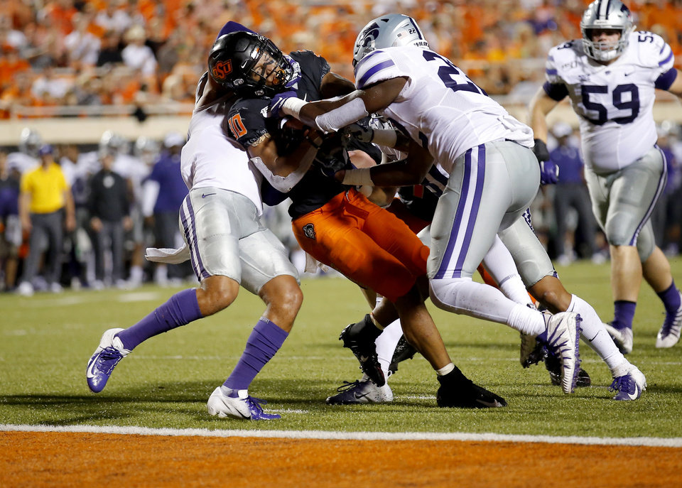 Photo - Oklahoma State's Chuba Hubbard (30)fights Kansas State's Denzel Goolsby (20) to the goal line in the fourth quarter during the college football game between the Oklahoma State Cowboys and the Kansas State Wildcats at Boone Pickens Stadium in Stillwater, Okla., Saturday, Sept. 28, 2019. The play was called back because of a penalty. OSU won 26-13. [Sarah Phipps/The Oklahoman]