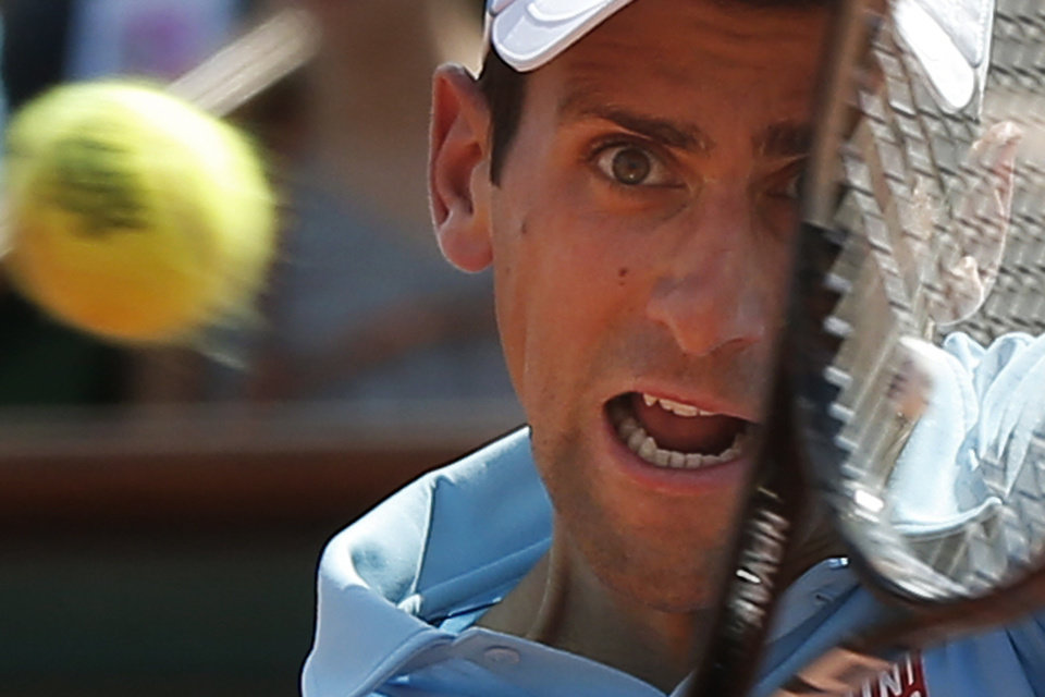 Photo - Serbia's Novak Djokovic returns the ball during the final of the French Open tennis tournament against Spain's Rafael Nadal at the Roland Garros stadium, in Paris, France, Sunday, June 8, 2014.  (AP Photo/Michel Euler)