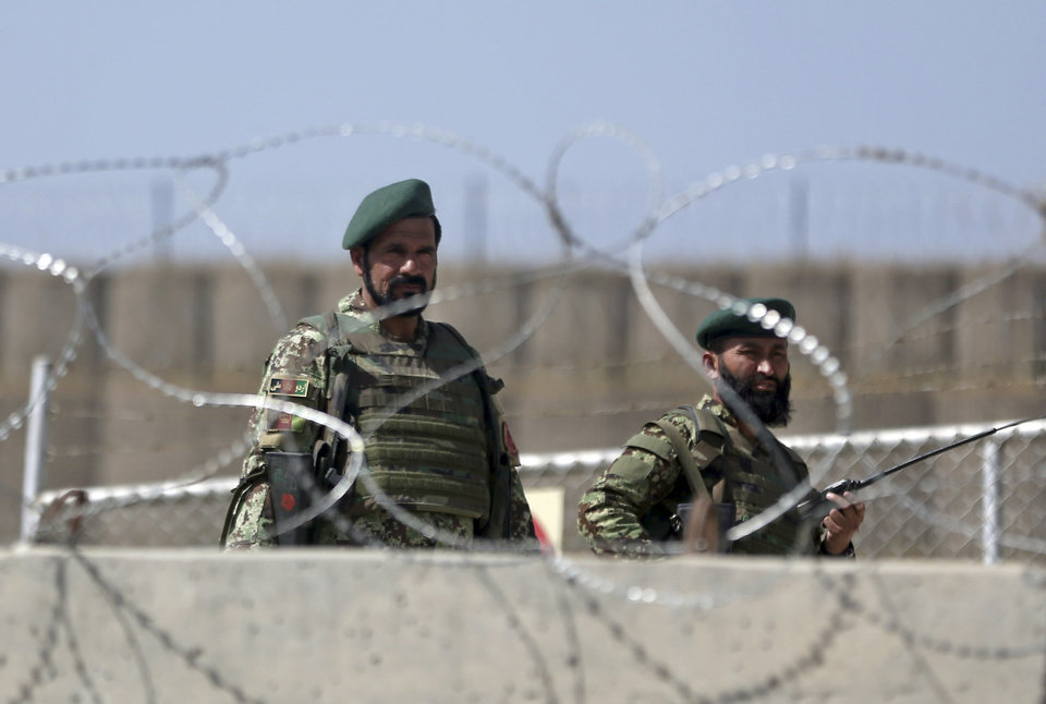 Photo - Afghanistan National Army soldiers stand guard at a gate of Camp Qargha, west of  Kabul, Afghanistan, Tuesday, Aug. 5, 2014. A man dressed in an Afghan army uniform opened fire Tuesday on foreign troops at a military base, causing casualties, an Afghan military spokesman said. In a statement NATO said it was investigating an