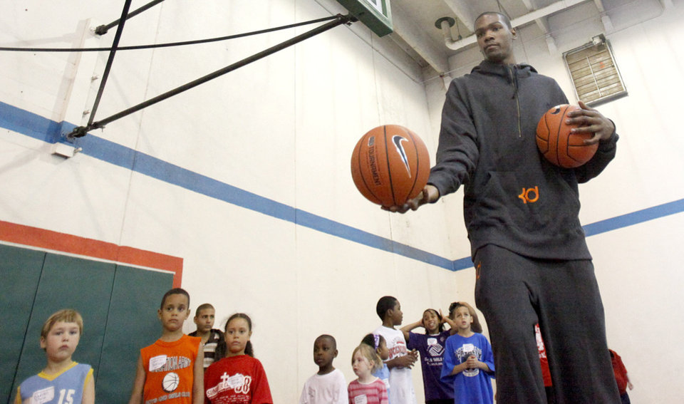 Photo - Kevin Durant helps players with shooting drills during the Nike Clinic at the Salvation Army Boy and Girls  Club, Saturday, Feb. 7, 2009, in Oklahoma City. PHOTO BY SARAH PHIPPS, THE OKLAHOMAN