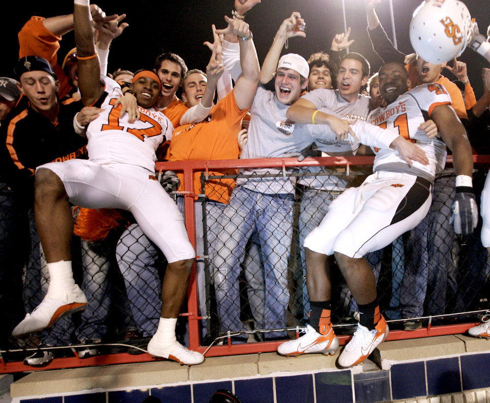 Photo - CELEBRATION: Jacob Lacey, left, and Orie Lemon celebrate with fans after OSU's win in the Oklahoma State University Cowboys (OSU) college football game against the University of Alabama Crimson Tide (UA) in the PetroSun Independence Bowl at Independence Stadium, on Thursday, Dec. 28, 2006, in Shreveport, La.  By Bryan Terry, The Oklahoman  ORG XMIT: KOD