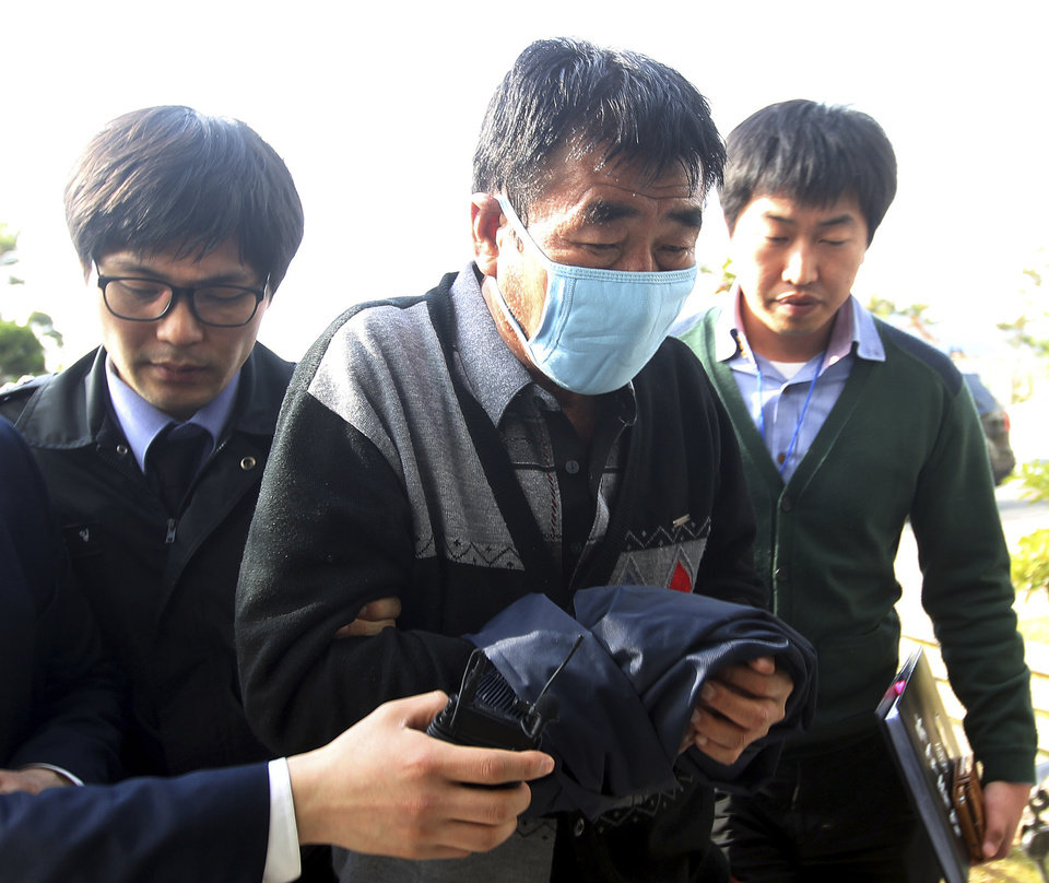 Photo - FILE - In this April 19, 2014 file photo, Lee Joon-seok, center, the captain of the sunken ferry boat Sewol in the water off the southern coast, arrives at the headquarters of a joint investigation team of prosecutors and police in Mokpo, south of Seoul, South Korea.  South Korea's prosecutors on Thursday, May 15, 2014, indicted 15 crew members over last month's ferry sinking, four of them on homicide charges, in a disaster has left more than 300 people dead or missing. (AP Photo/Yonhap, File) KOREA OUT