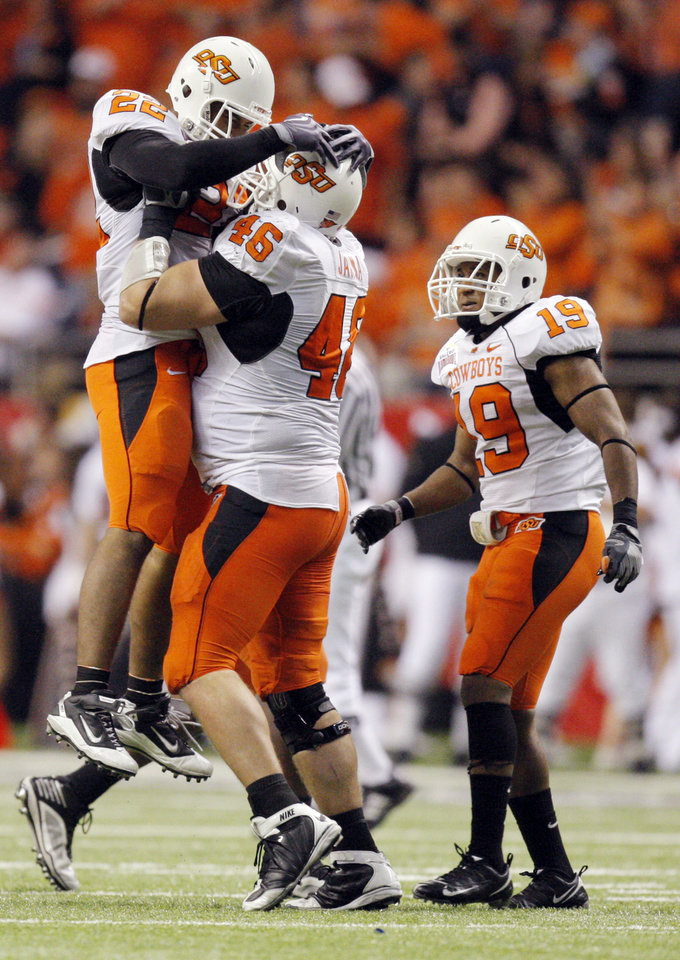 Photo - OSU's James Thomas (22) celebrates an interception with Shane Jarka (46) near Brodrick Brown (19) during the Valero Alamo Bowl college football game between the Oklahoma State University Cowboys (OSU) and the University of Arizona Wildcats at the Alamodome in San Antonio, Texas, Wednesday, December 29, 2010. OSU won, 36-10. Photo by Nate Billings, The Oklahoman