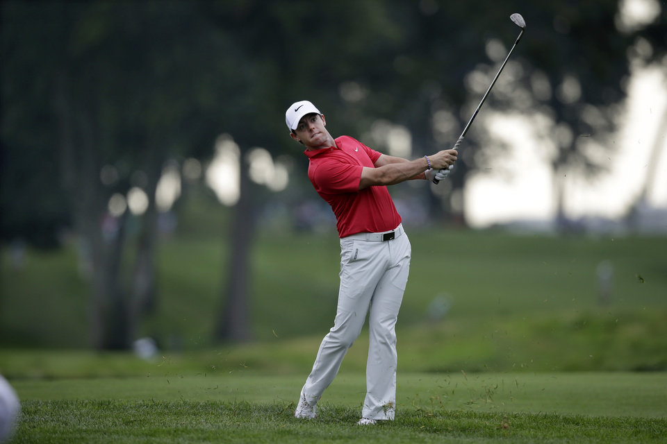 Photo - Rory McIlroy, of Northern Ireland, hits a fairway shot on the 13th hole during the first round of play at The Barclays golf tournament Thursday, Aug. 21, 2014, in Paramus, N.J.  (AP Photo/Mel Evans)