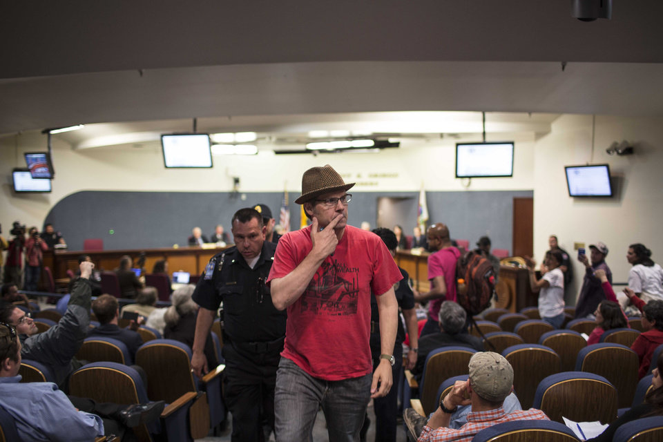 Photo - Activist David Correia motions to Albuquerque Police chief Gorden Eden as Correia is escorted from city council chambers in Albuquerque, N.M., Thursday, May 8, 2014. At least seven people were removed from the chambers and given a criminal trespass notice saying not to return to council chambers for 90 days. The Albuquerque City Council gathered Thursday under new rules and heightened security designed to avoid an angry confrontation like the one that broke out earlier in the week amid community outrage over a spate of deadly police shootings. (AP Photo/Juan Antonio Labreche)