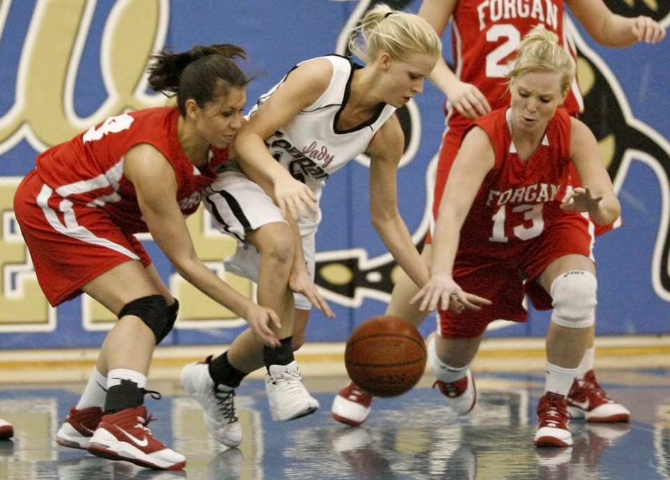 Photo - Caney's Kassi Baughman goes for the ball between Forgan's Miranda Lopez, left, and Jaci McGill during the Class B girls state basketball tournament at Choctaw High School in Choctaw, Okla., Thursday, March 4, 2010.  Photo by Bryan Terry, The Oklahoman
