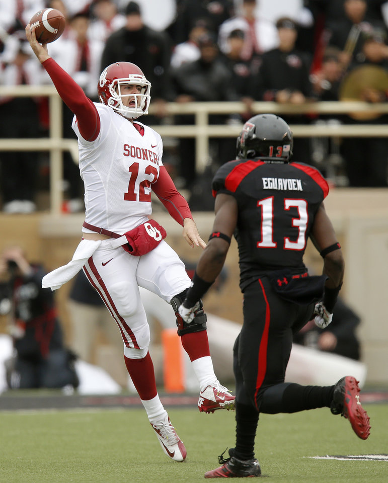 Photo - Oklahoma's Landry Jones (12) throws a pass over Texas Tech's Sam Eguavoen (13) during a college football game between the University of Oklahoma (OU) and Texas Tech University at Jones AT&T Stadium in Lubbock, Texas, Saturday, Oct. 6, 2012. Photo by Bryan Terry, The Oklahoman