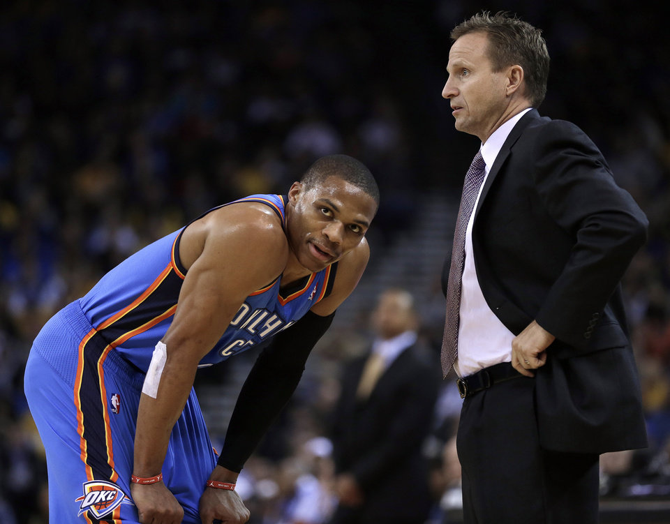 Photo - Oklahoma City Thunder coach Scott Brooks, right, speaks with Russell Westbrook during the first half of an NBA basketball game against the Golden State Warriors, Thursday, Nov. 14, 2013, in Oakland, Calif. (AP Photo/Ben Margot)