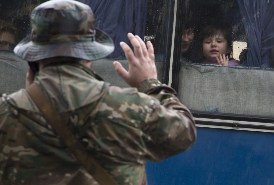Photo - A Donetsk People's Republic fighter tells goodbye to his family departing as refugees to Russia in the city of Donetsk, eastern Ukraine Monday, July 14, 2014. Five busloads of Internally Displaced People from the towns of Slavyansk, Karlovka, Maryinka and Donetsk left here Monday morning for the Rostov region in Russia to ask for refugee status there. (AP Photo/Dmitry Lovetsky)